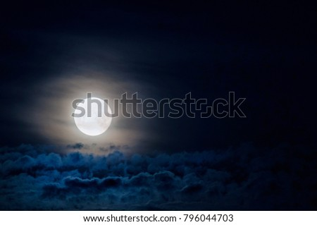 Dramatic photo illustration of a nighttime sky with brightly lit clouds and large, bright full moon. A great background. #796044703