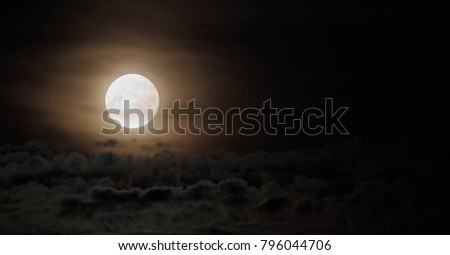 Dramatic photo illustration of a nighttime sky with brightly lit clouds and large, bright full moon. A great background. #796044706