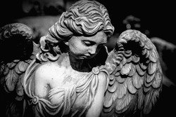 Dramatic photo of sad angel with deep shadows. Fragment of ancient statue. Death and pain concept. Horizontal image.