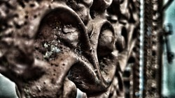 Dramatic photo plant, vintage and monocrome effect Iron carving of a circular house fence with worn brown paint, aesthetically pleasing old building art
