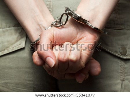 Dramatic photograph of woman´s hands in handcuffs (close-up)