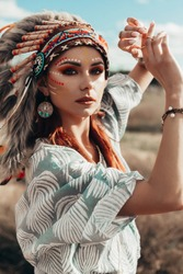 Dramatic portrait of a beautiful  lady  in an Indian headdress. Cap of the leader of the Indian. Roach. Bright makeup, painted face, boho style, feathers, accessories