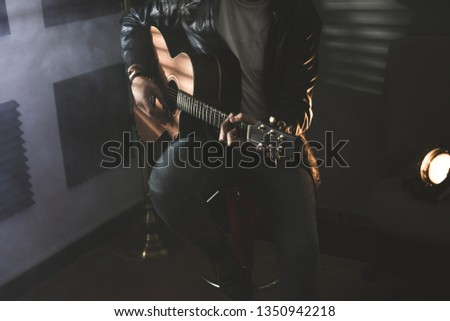 Dramatic portrait of a man playing a guitar. Guitarist concept