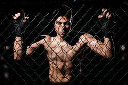 Dramatic portrait of a MMA Fighter grabbing the fighting cage and intimidating his opponents