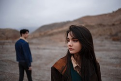 Dramatic portrait of a young brunette girl in cloudy weather. somewhere behind her, out of focus, her young lover boyfriend leaves her after break up . selective focus, small focus area.