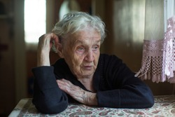Dramatic portrait of an old gray-haired woman sitting at a table in house.