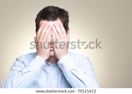 Dramatic portrait of desperate sad man in pain hiding his face