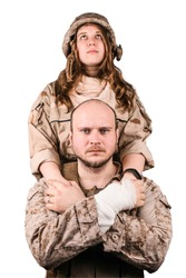 Dramatic portrait of male and female soldiers. Girl looking up white holding hands of injured man soldier, who is looking into camera. They dressed in pixel desert combat uniform. Isolated, white bg.