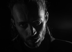 Dramatic portrait of male person looking at camera on dark background