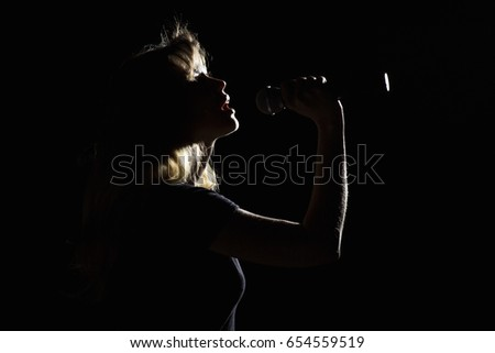 Dramatic portrait of young woman singing into microphone on black background under light of a lantern #654559519