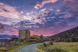 Dramatic purple and pink dawn breaking over an old farm building in the Balagne region of Corsica with a small tarmac road passing by and snow capped mountains in the distance