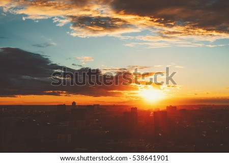 Dramatic red scenery of city silhouette at sunset with strong sun flare, teal sky with clouds and rays of light coming through buildings #538641901