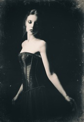 Dramatic retro portrait of a beautiful sad gothic girl among the dark. Old film effect, black and white