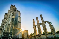 Dramatic Saint Bertin abbey ruins in Saint-omer in France during the sunrise with sun flare on the backgroudn.No poeple. Empty spce background.