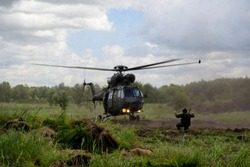 Dramatic scenario on a battlefield with a soldier standing on the field, meadow, of pastureland and directs a flying helicopter (chopper) to allow it for smooth landing in cloudy and stormy conditions