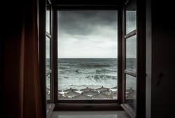 Dramatic sea view from opened window with big stormy waves and dramatic sky during rain and storm weather in fall season on sea coast