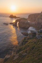 Dramatic seascape landscape of Enys Dodnan sea arch at rocky coastline of Land's End at sunset in Cornwall, England, UK.