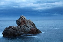 Dramatic seascape Rock against the sea and blue sky in the evening