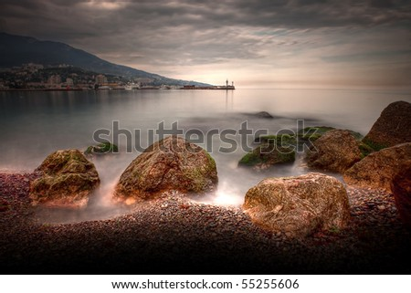 dramatic seascape with rocky beach and lighthouse - stock photo