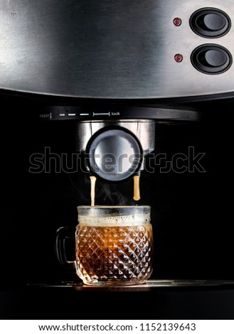 Dramatic shot of an espresso machine, closeup, brewing fresh coffee on a glass cup, with steam smoke coming out