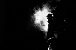 dramatic silhouette of a dangerous man in a hat at night in the rain in the city in the old crime