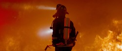 Dramatic silhouette of American firefighter in full gear exploring the huge fire zone