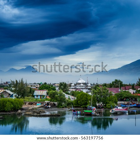 Dramatic skies and mosque in lush landscape in Banda Aceh, Sumatra, Indonesia #563197756