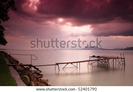 Dramatic sky and sunbeam over Lake Balaton in Hungary with landing stage