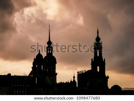 Dramatic sky and the contours of a famous building/landmark in Dresden, Saxony, Germany: Haumannsturm and the Residenzschloss/Dresden Castle to the left, the Hofkirche/Catholic Church to the right. #1098477680