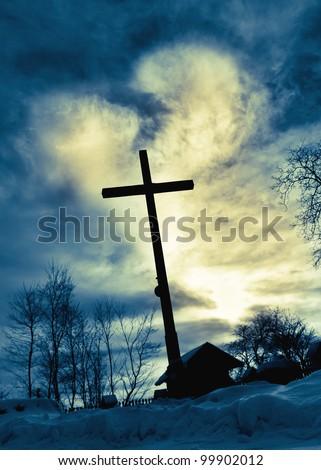 Dramatic sky cloud with deep blue  heart shape shining behind Jesus cross