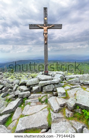 Dramatic sky over a Cross on a Lusen peak (1373m) in national park Bavarian Forest. Germany, Europe.