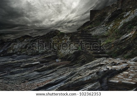 Dramatic sky over steps in a mountain.