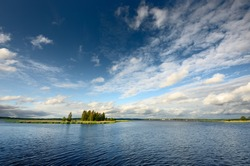 Dramatic sky with cirrus and cumulus clouds above the blue lake and island with green birch trees before the rain. Idyllic summer scene. Panoramic view. Vacations, ecotourism, nature of Scandinavia