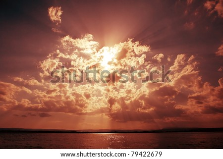 Dramatic sky with clouds and sun beams over ocean