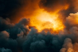 Dramatic sky with dark clouds and orange light from sunset, background