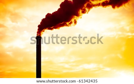 Dramatic smoke from an industrial chimney at sunset