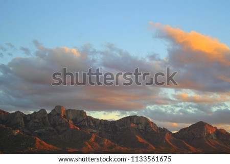Dramatic, Soft pastel blue and pink sunset monsoon clouds over the Santa catalina mountains in Catalina State Park tucson arizona