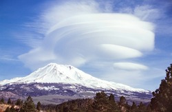 dramatic spectacular lenticular cloud formation over mount shasta in california with trees in the foreground