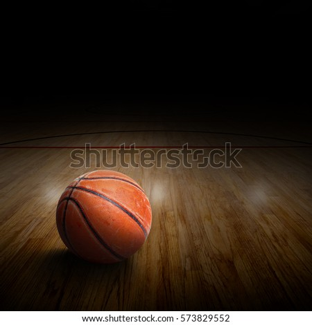 Dramatic spot lighting on basketball arena with rugged and seasoned ball on court and copy space.