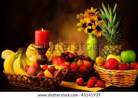 Dramatic still life of assorted fruits and garlic bread rolls