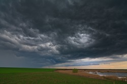 Dramatic storm sky and ominous clouds over lake in April