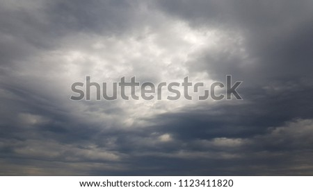 Dramatic stormy cloudscape with dark blue gray clouds. Sunlight through overcast weather clouds. Summer storm weather.