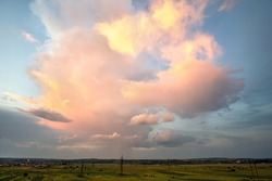 Dramatic stormy sunset over rural area with puffy clouds lit by orange setting sun and blue sky.