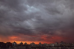 Dramatic stormy sunset sky with clouds over city skyline background.
