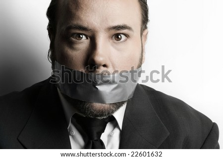 Dramatic stylized close-up of a very businessman with duct tape covering his mouth
