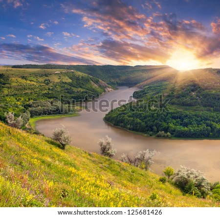 Dramatic summer sunrise near the river in the mountains