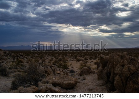 dramatic sunbeams penetrated the cloudcover over the desolate mojave desert #1477213745