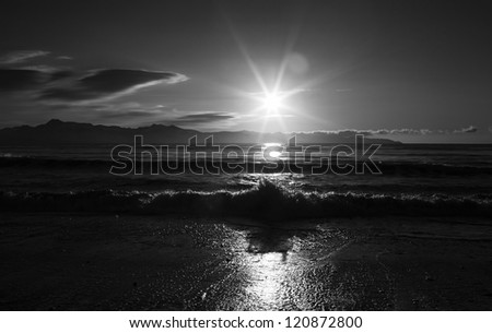 Dramatic sunburst with the shadow of a splashing wave on an Alaskan beach in black and white.