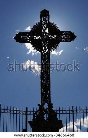 Dramatic sunlight behind a cruz in a small village of Provence (French Riviera)