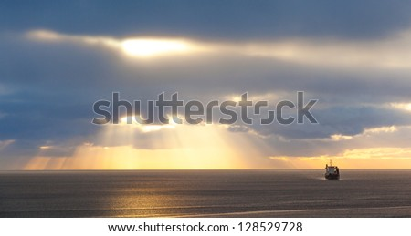 Dramatic sunrise at the Sea. Alone ship under sun rays through the clouds. Azores, Ponta Delgada, San Miguel (Sao Miguel)
